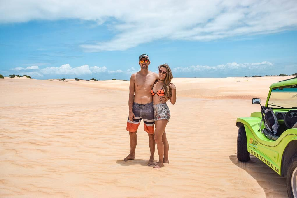 Bailey and daniel stand next to their dune buggy on the tour from Natal, Brazil
