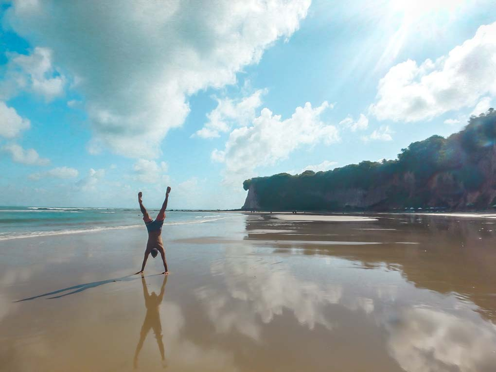 Daniel does a handstand at a beach in Pipa, Brazil