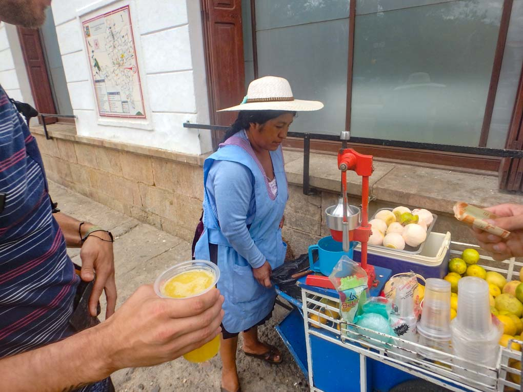 Buying a fresh orange juice from a street seller in Sucre, Bolivia