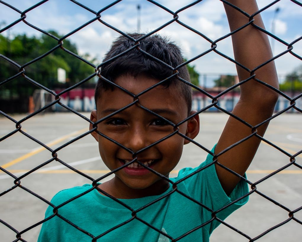 A boy looks througha  fence and smailes at the camera in Medellin, Colombia
