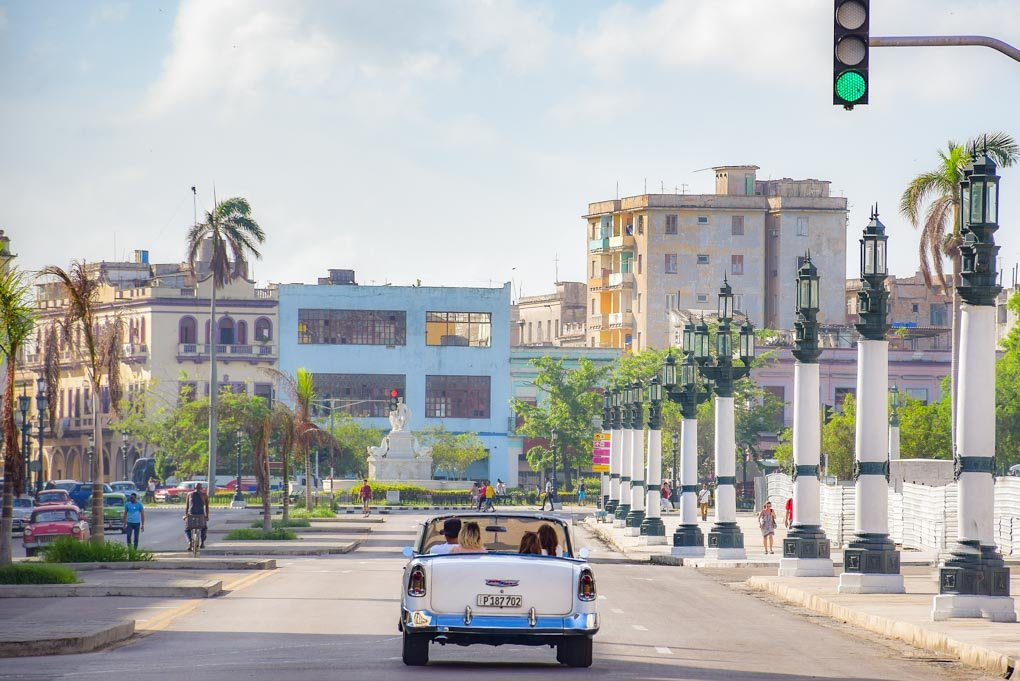 A car drives down a road in the old city of Havana, Cuba