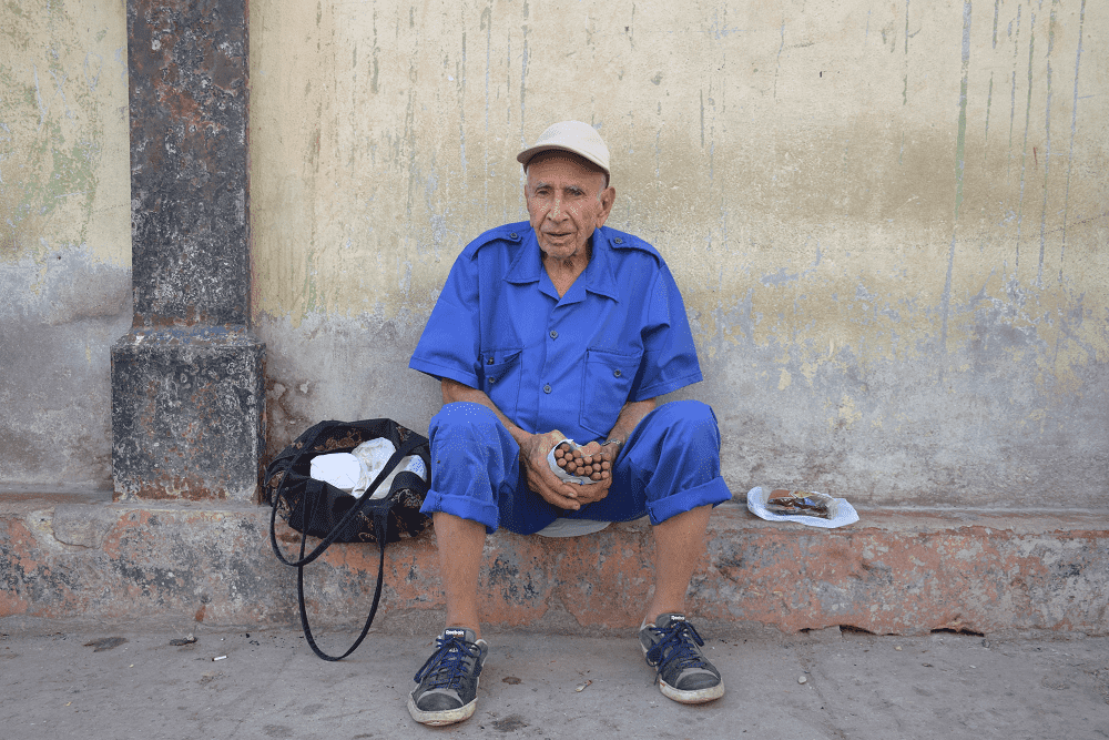 An old man sells cigars on the street