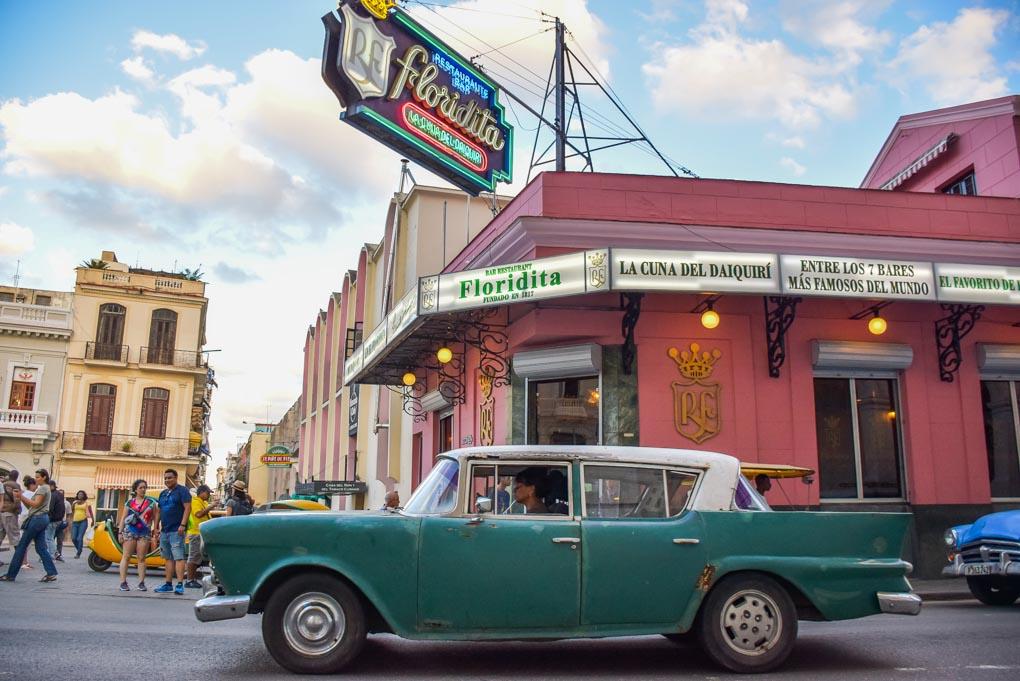 An old car drives past the La Bodeguita del Medio bar in Havana