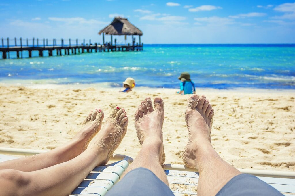 couples feet at a beach in Cozumel
