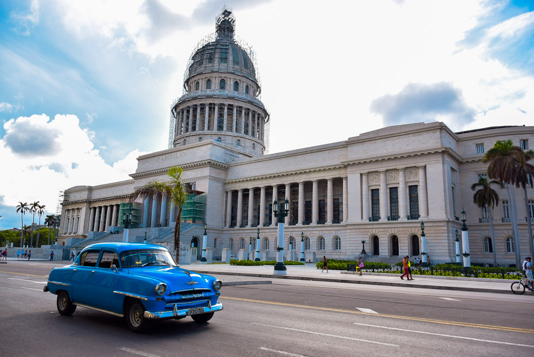 the capital building in Havana cuba with a blue vintage car in front