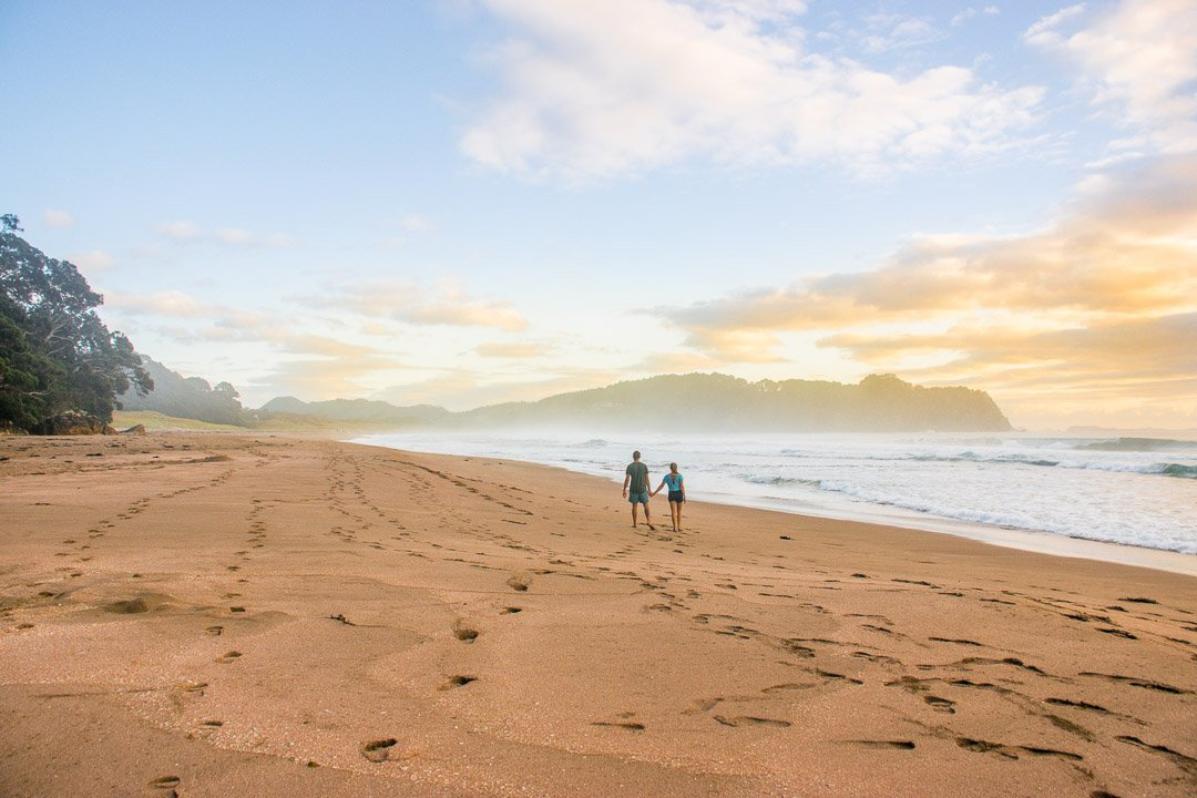 Two people walk along Hot Water Beach, New Zealand