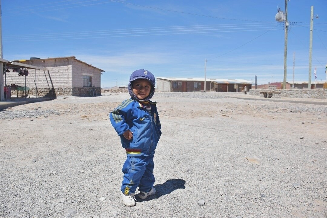 a cute kid posing for the camera on the slat flats in bolivia