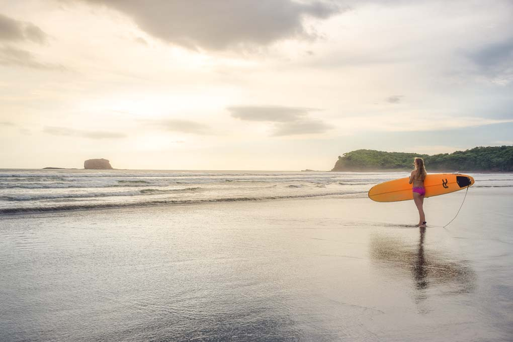 Bailey prepares to enter the water with a surfboard in San Juan del Sur, Nicaragua
