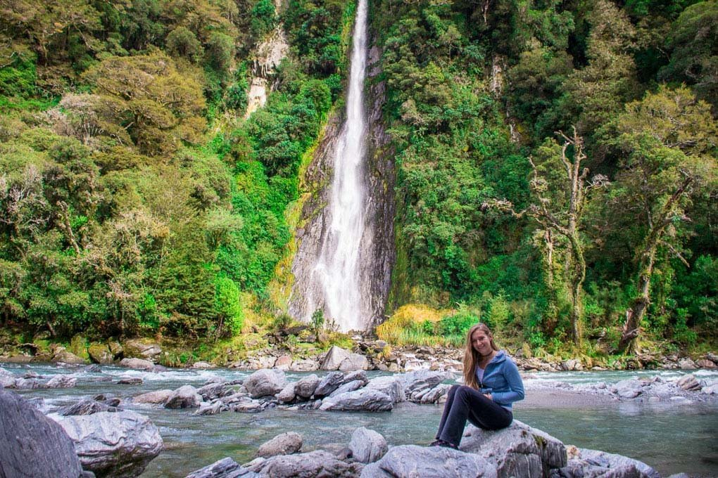 A woman sits on a rock in front of Thunder Creek Falls in New Zealand