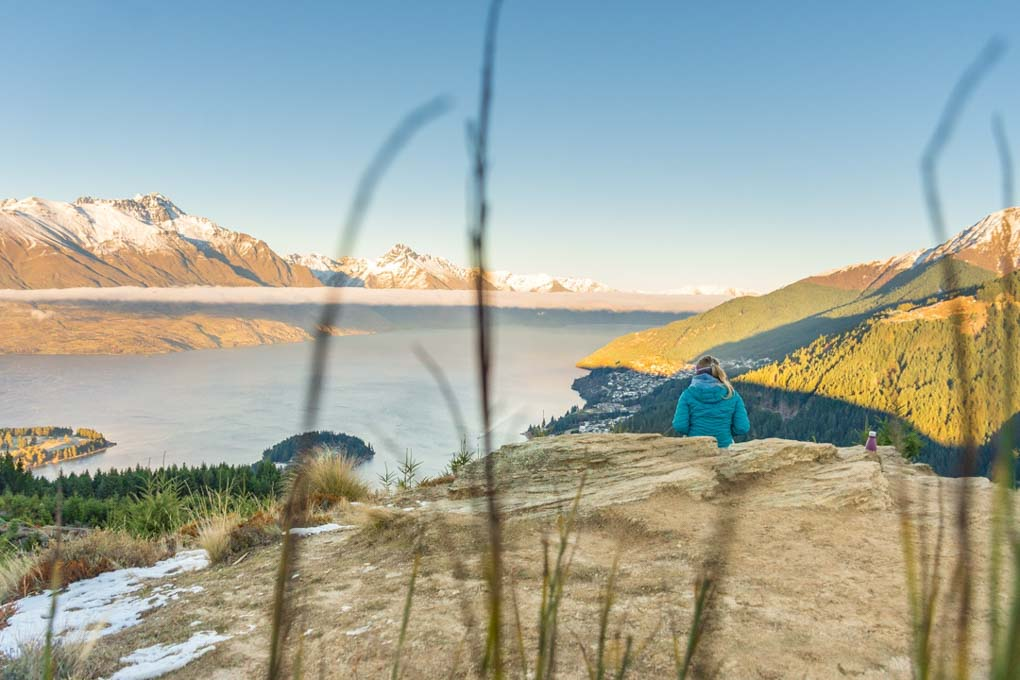 A woman watches a sunrise from the top of Queenstown Hill in Queenstown