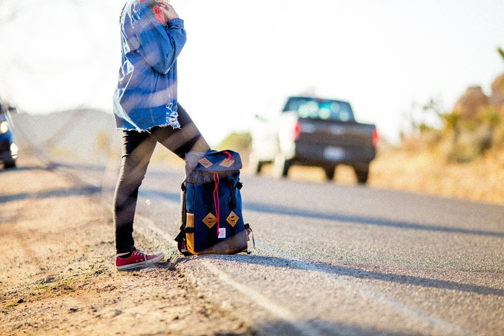 girl hitchhiking with backpack on the side of the road