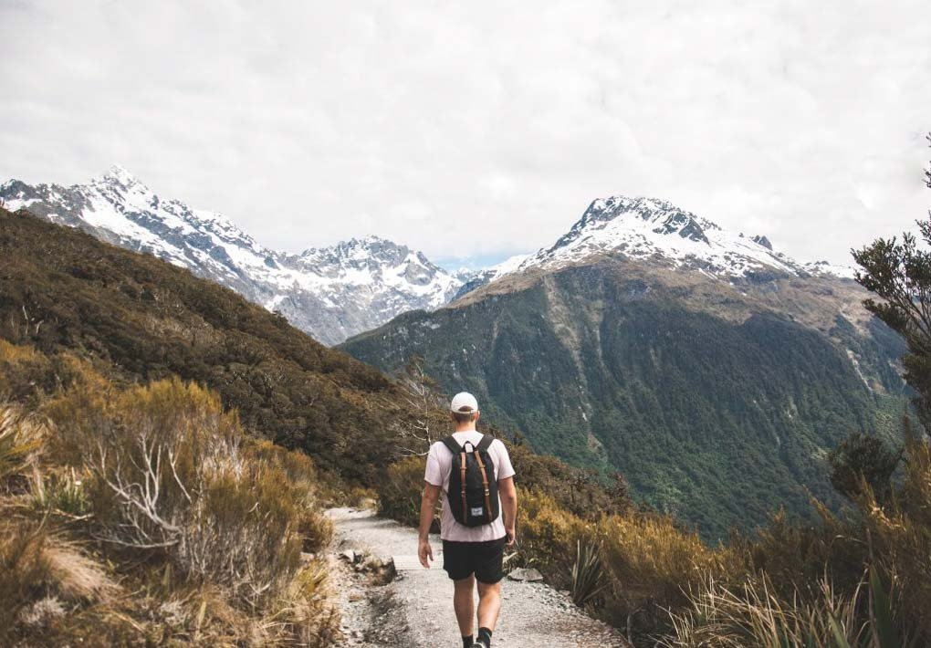 A man walks along the trail of the key Summit on the road to Milford Sound