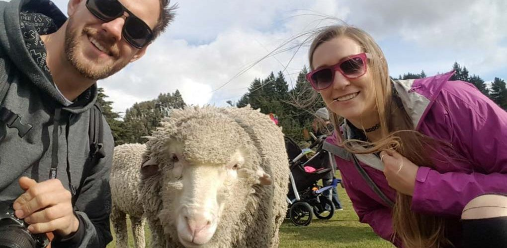 Bailey and Daniel from Destinationless Travel pose for a photo with a sheep in New Zealand