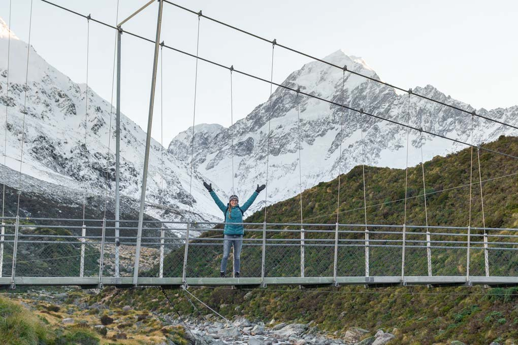 Bailey standing on a suspension bridge on the Hooker Valley Trail with Mount Cook in the background