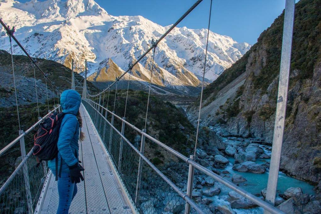 A woman stands on the Hooker Valley track suspension bridge looking towards Mt Cook