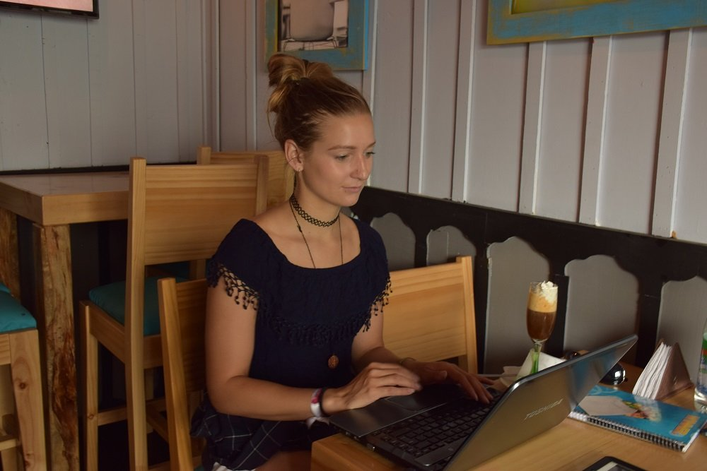 woman sitting at a desk in a cafe working on the computer