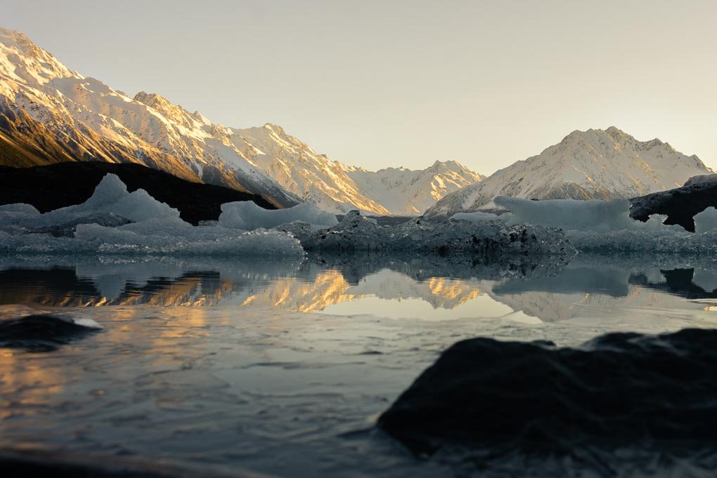 The Tasman Glacier and Tasman Lake just as the sun appears behind the mountains