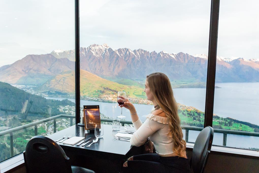 Bailey sits at our table with a glass of wine at the Stratosfare Restaurant in Queenstown