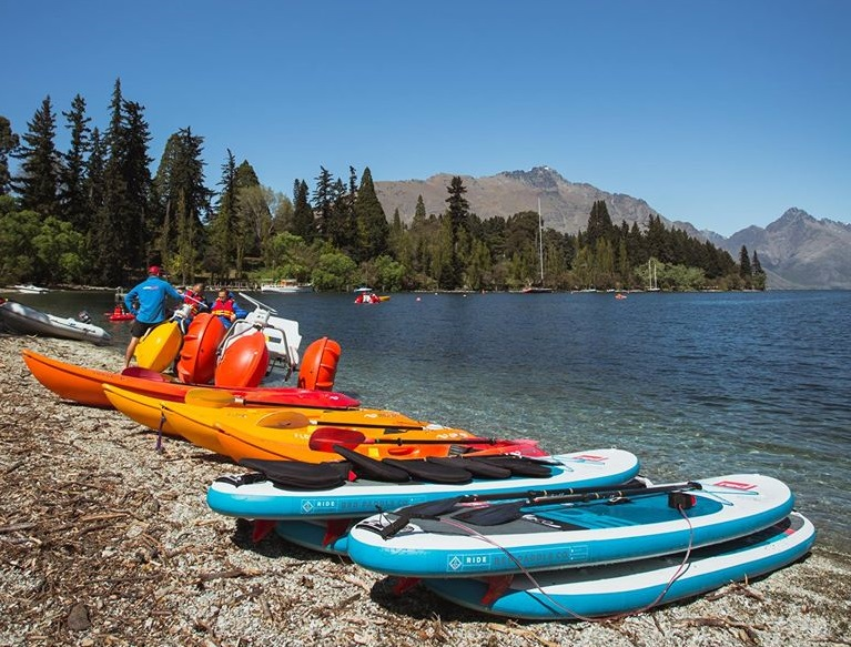 Paddel boards and kayaks on the shore of Lake Wakatipu during a Queenstown summer