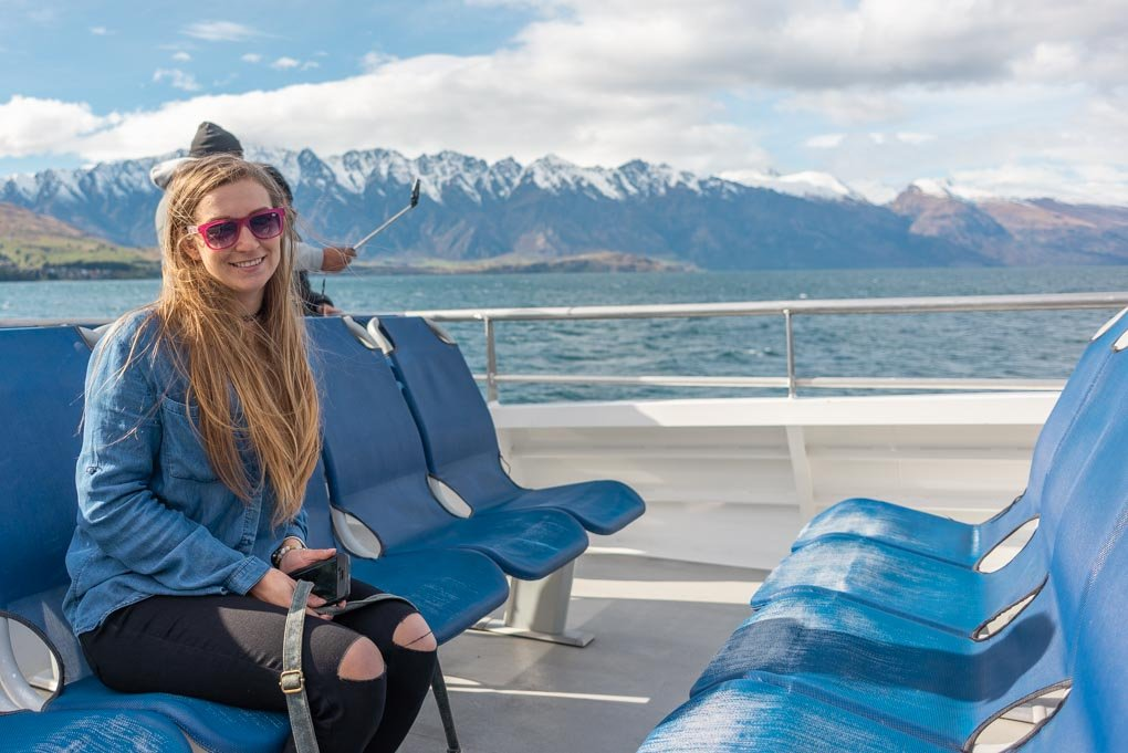 Bailey sits on the Spirit of Queenstown Scenic Cruise with the Remarkables mountain range in the background