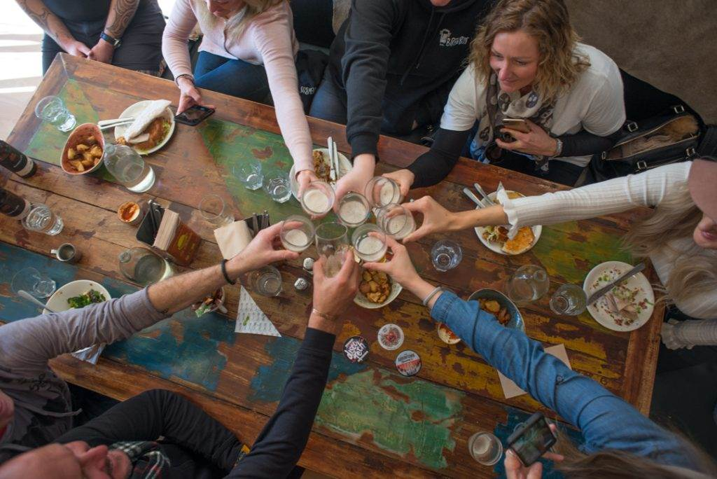 People cheers each other on a table at a brewery in New Zealand on a craft beer tour
