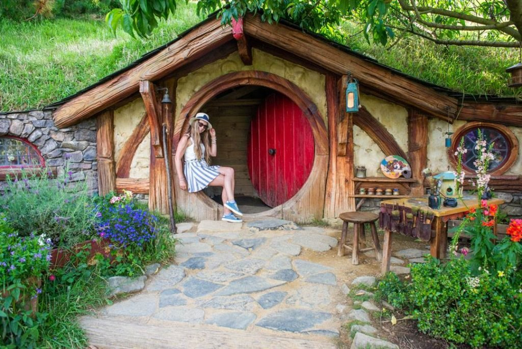 Bailey sitting in the door of a Hobbit hole at the Hobbiton Movie set in New Zealand