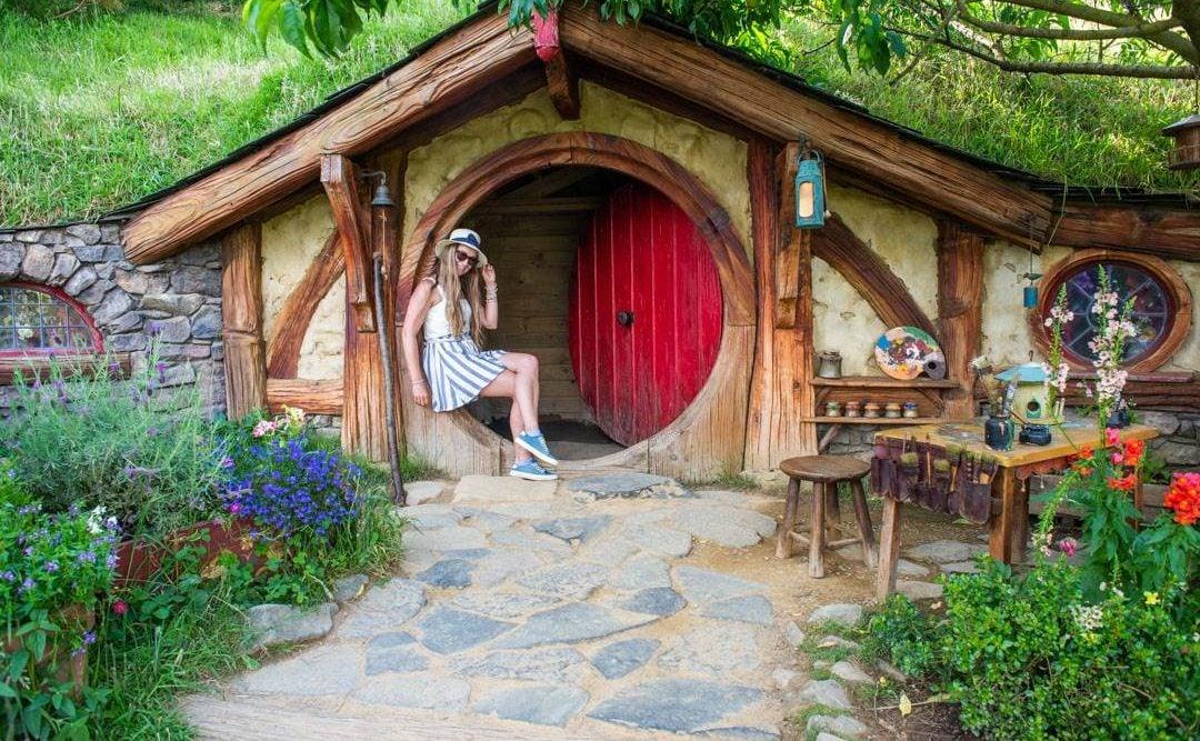 Bailey sits in a Hobbit door at Hobbiton in New Zealand