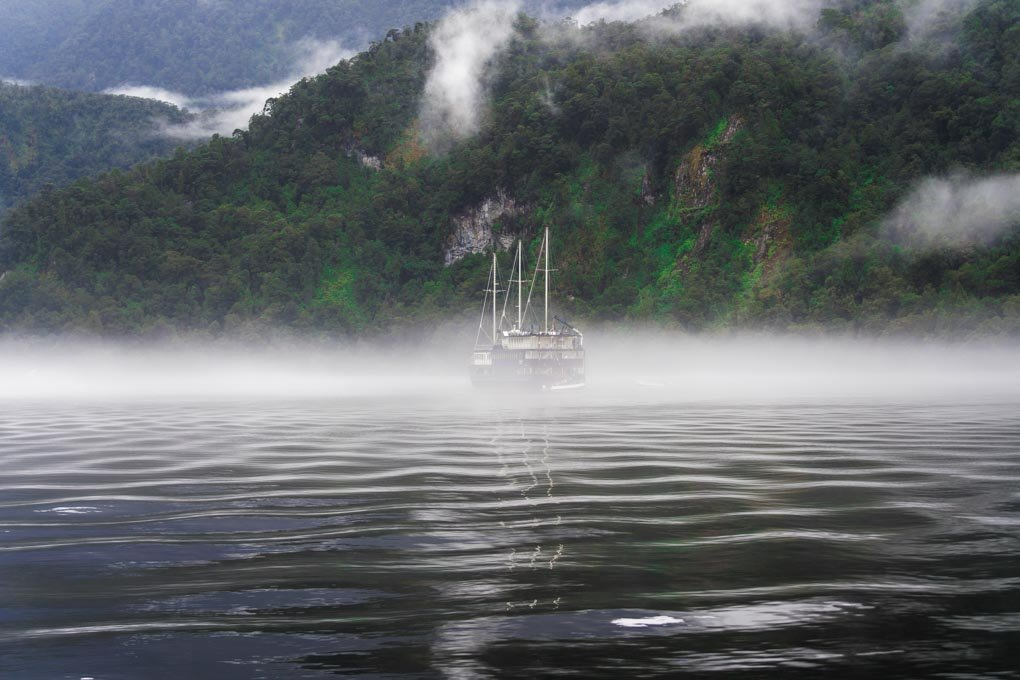 A boat cruises through Doubtful Sound in New Zealand