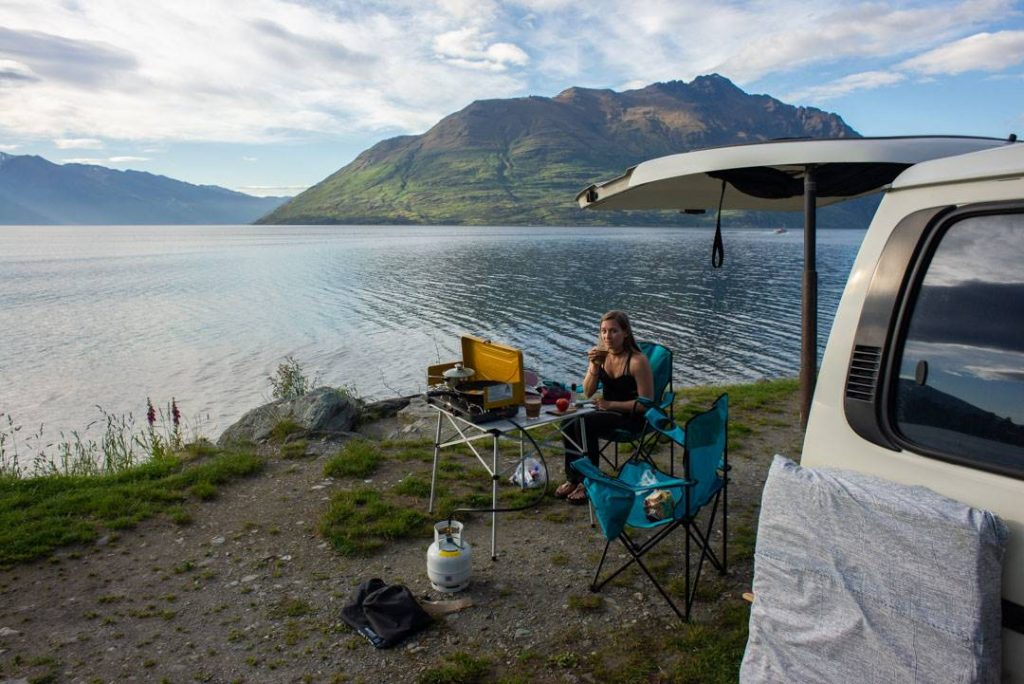 A lady sits by her camper van in New Zealand