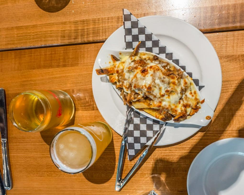 A plate of loaded poutine and beer at one of the restaurants we visited on our Vancouver food tour