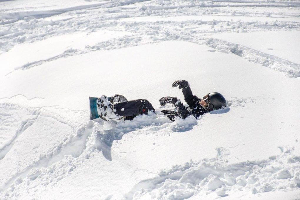 A man sits in the snow with his snowboard