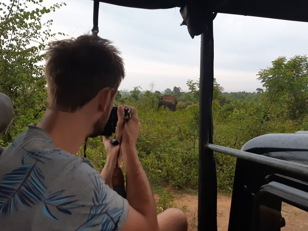 taking a photo of an elephant in Udawalalwe national park while on a jeep safari