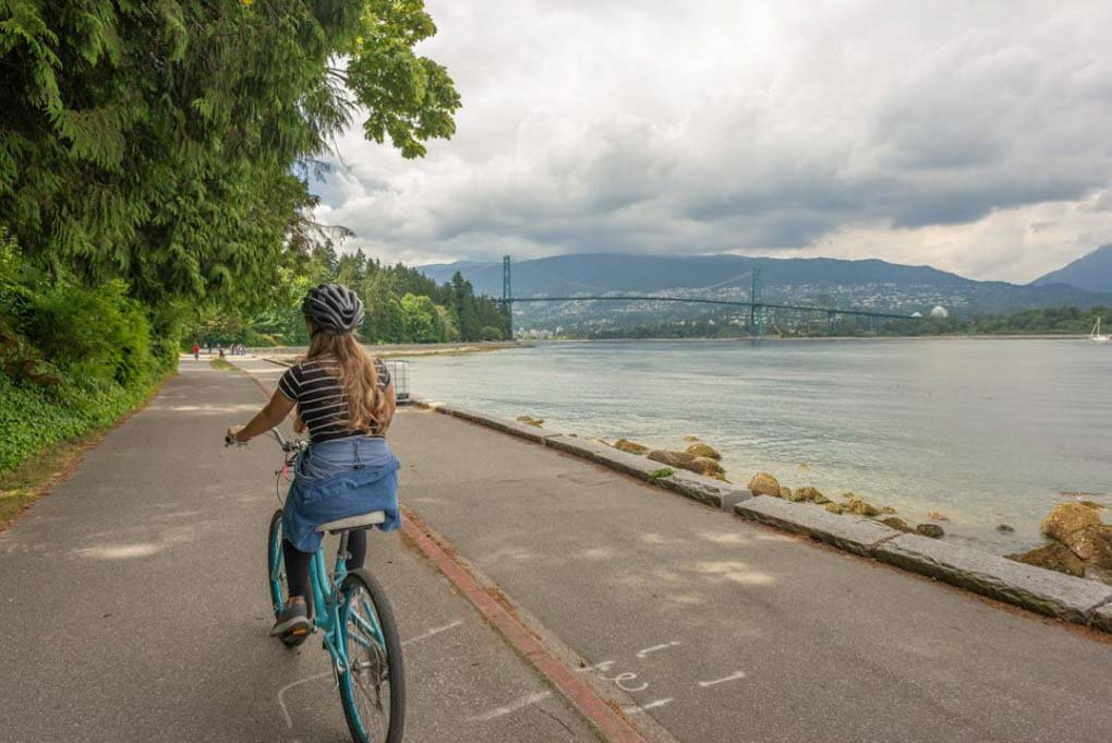 A lady rides her bike along the seawall in Stanley Park, Vancouver, Canada