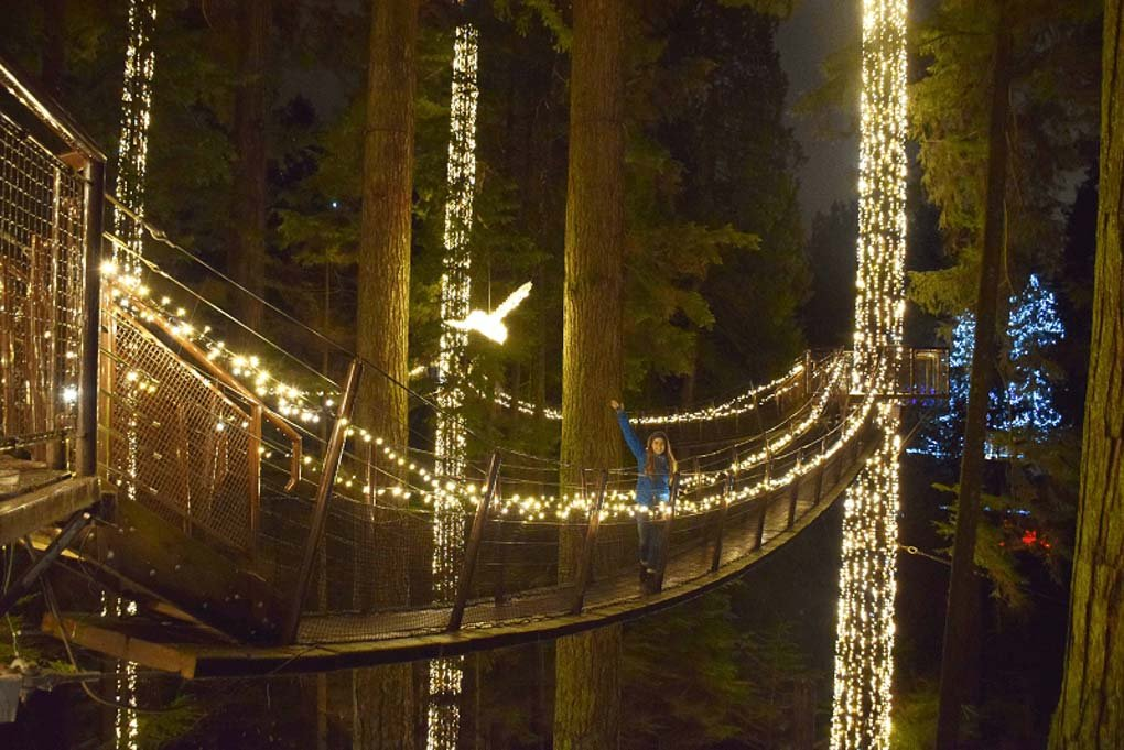 A lady poses for a photo on the Capilano Suspension Bridge Walk at night