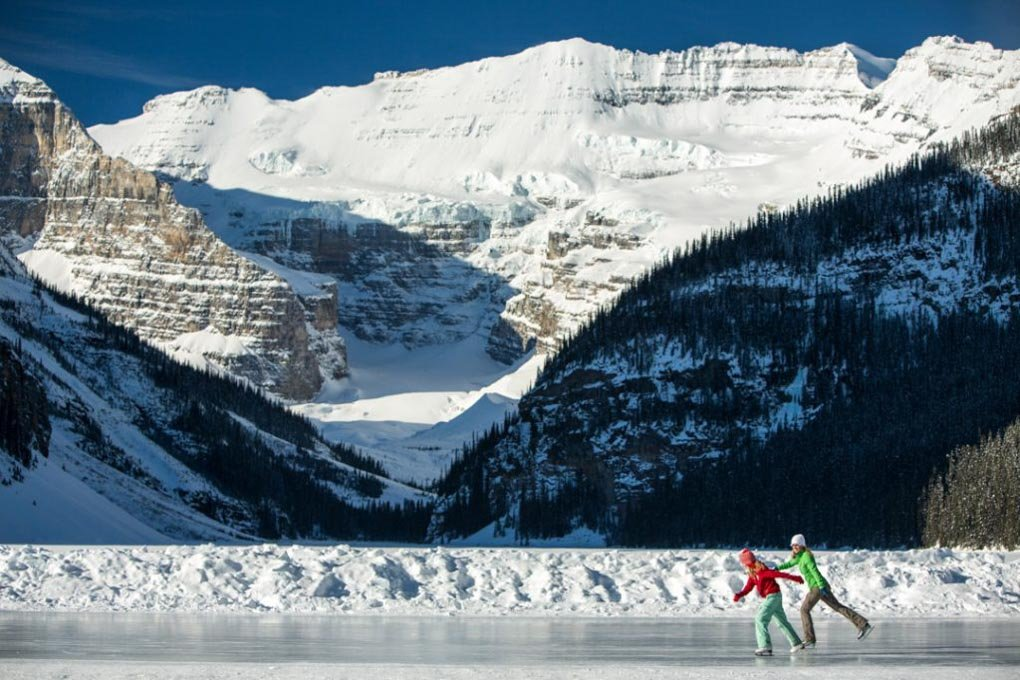 two people ice skate on a frozen lake in Banff