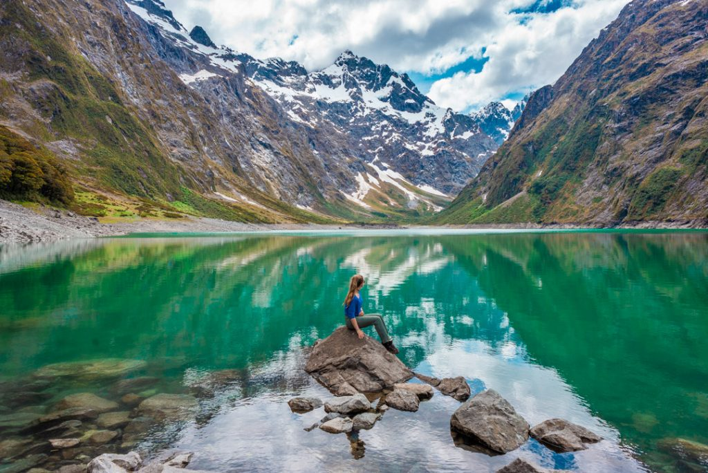 Lady sitting on a rock at Lake Marian in Fiordland National Park, New Zealand