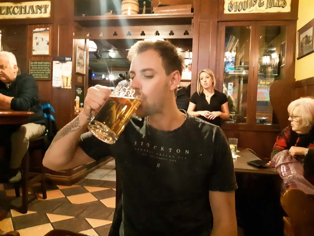A man drinks a beer at the Irish Pub in Banff, Canada on a night out