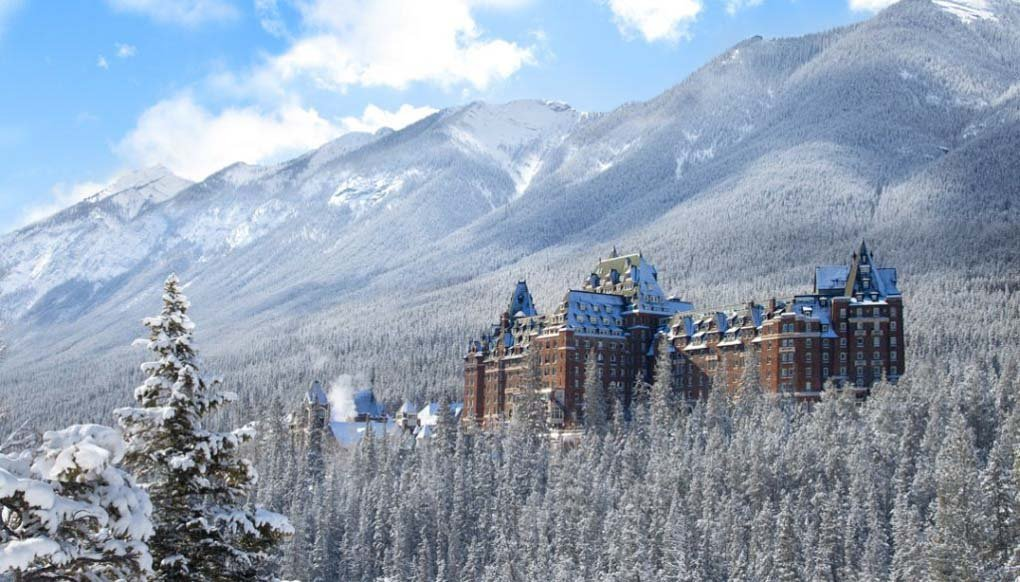 The Fairmont Springs hotel on a winters day wit the mountains behind it