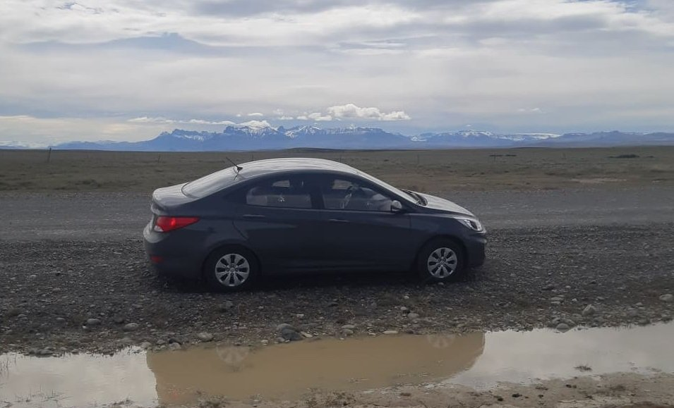 car parked on the side of a gravel road in patagonia