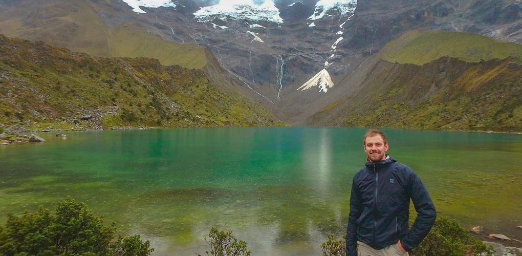 Standing at a lake on the Salkantay Trek