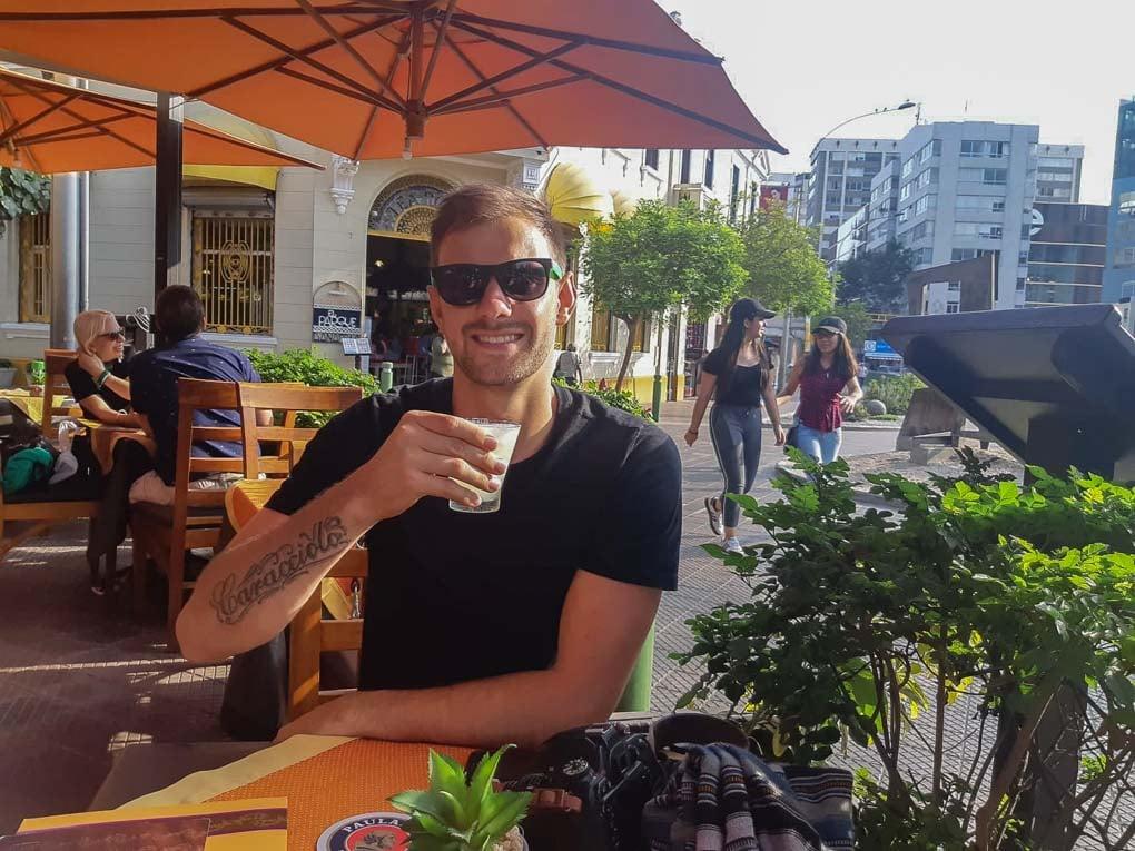 daniel drinking a pisco sour in peru