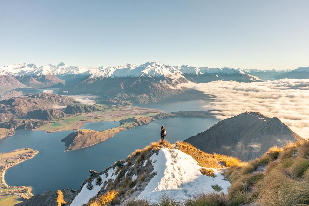 Bailey stands on Roy's Peak, New Zealand at sunrise