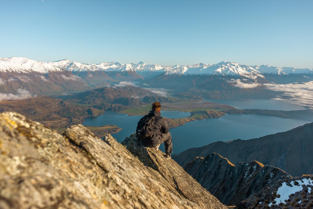 A man sits on a rock at Roy's Peak and enjoys the views
