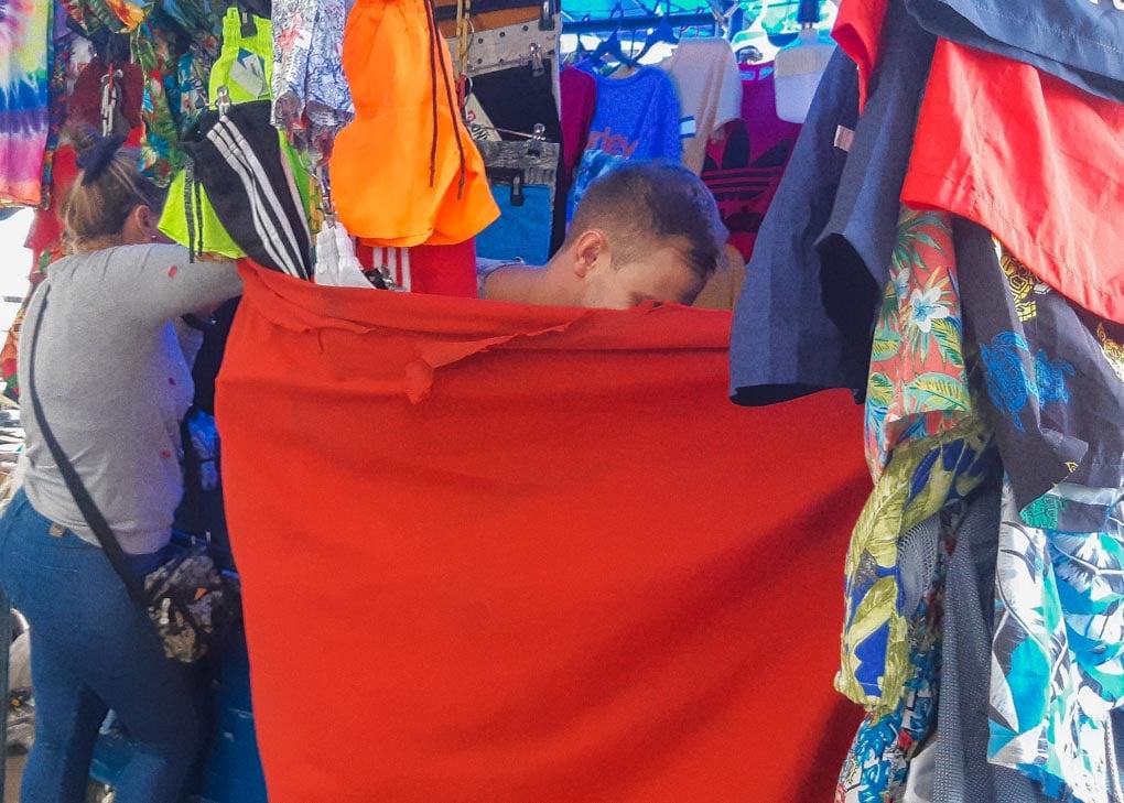 Daniel changes in a makeshift cvhangeroom at the street markets of Santa Marta