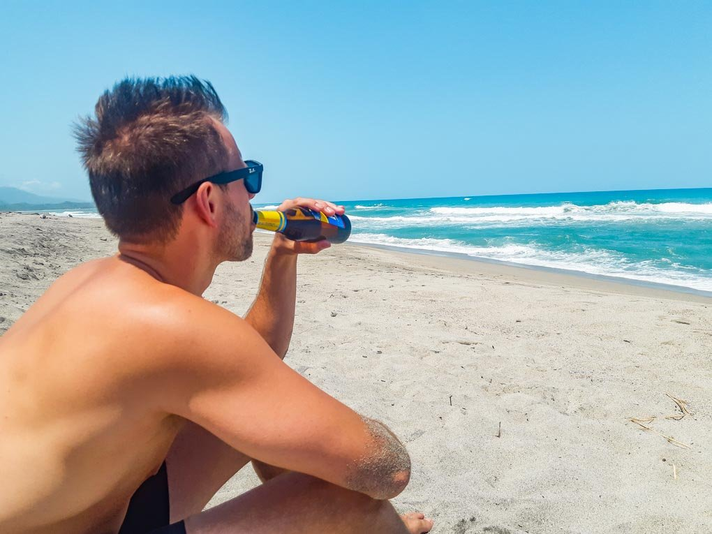 Daniel enjoys a beer on Palomino Beach, Colombia