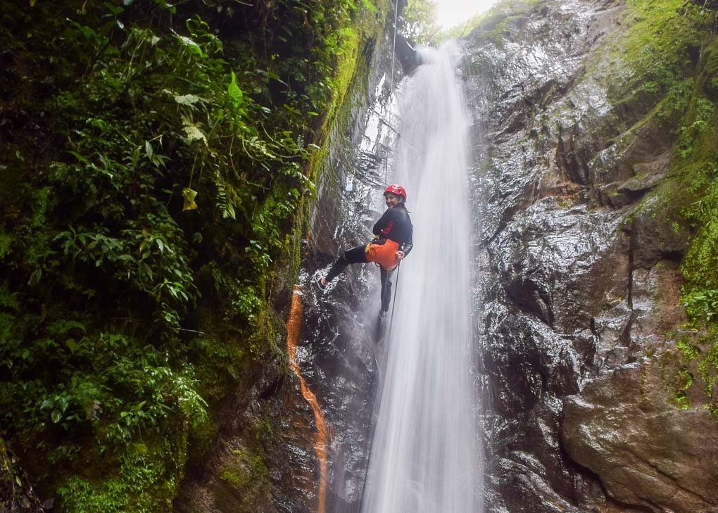 A lady repels down a waterfall while Canyoning in Banos, Ecuador
