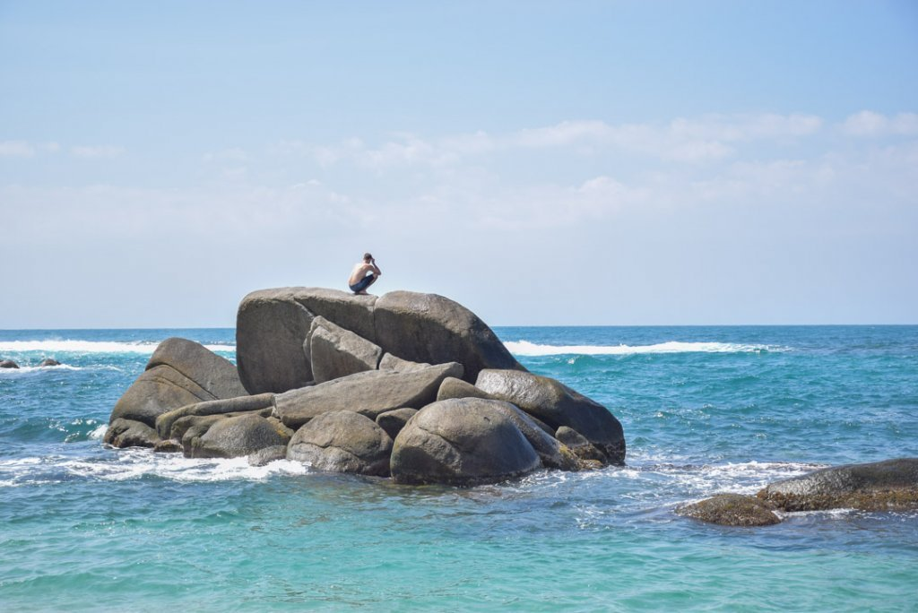 A man sits on a rock in the ocean at Cabo San juan Beach.