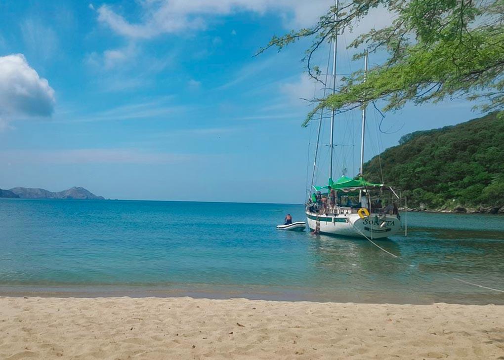 A sail boat is anchored up at a beach in Tayrona National park after sailing from Santa Marta
