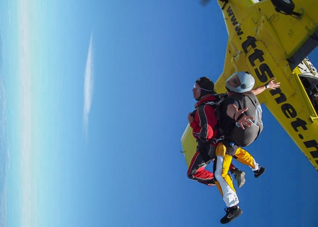A person leaves the plane on a skydive in the Bay of Isalnds.