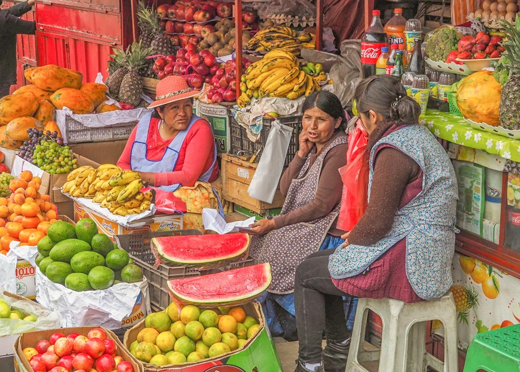 Two ladies sit at a market stall in Bolivia